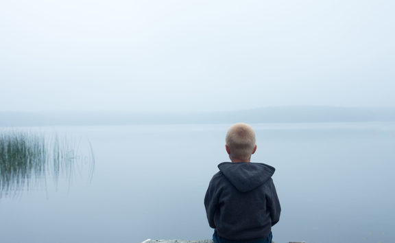 47556115 - sad child sitting alone by lake in a foggy day, back view