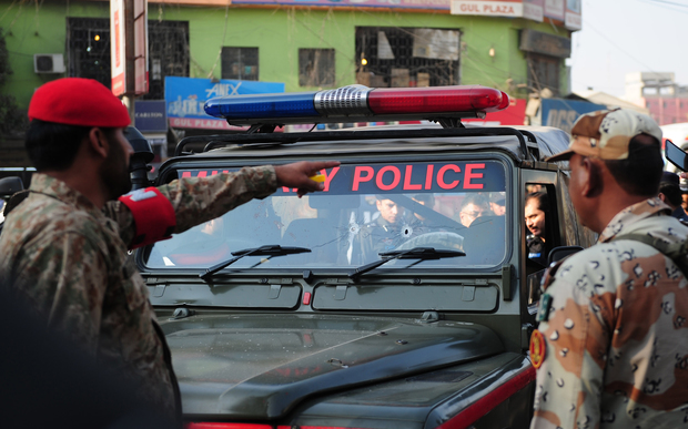 Pakistani security officials inspect a military police jeep following an attack by gunmen in Karachi on 1 December 2015.