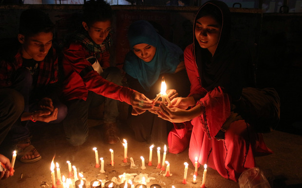The Pakistani Civil Society light candles at a vigil in Karachi for the victims of last year's school attack by Taliban militants in Peshawar, on December 16, 2015.