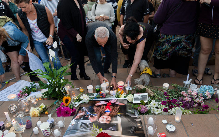 People place candles and flowers next to a photo of British backpacker Grace Millane during the vigil at Civic Square Park in Wellington.