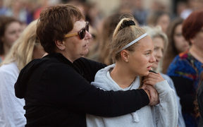A woman with her daughter stand as a song is played during a vigil for Grace Millane at Civic Square Park in Wellington.