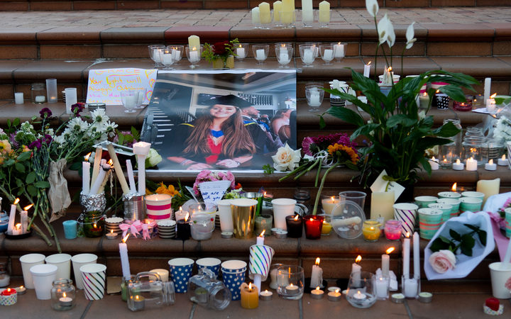 Candles and flowers are laid next to a photo of Grace Millane during the vigil at Civic Square Park in Wellington.