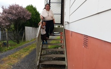 Gia Seuseu and her youngest son on the steps of her Glen Eden home.