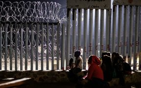 Migrants from Guatemala, part of the Central American migrant caravan, are seen near the US-Mexico border fence in Mexico on December 9, 2018. -