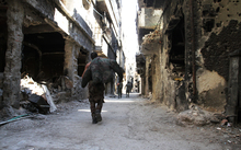 Men walk past destroyed buildings in the Yarmuk Palestinian refugee camp in the Syrian capital Damascus on April 6, 2015.