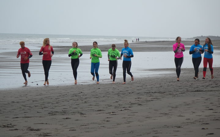 Otorohanga College Year 10 students warm up before a surfing session at Fitzroy Beach.