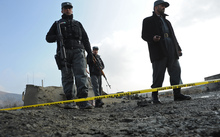 Afghan police stand guard at the site of a suicide attack near a NATO military convoy entering Kabul airport on December 11, 2013.