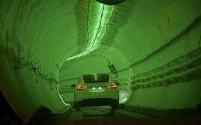A modified Tesla Model X drives into the tunnel entrance before an unveiling event for the Boring Co.