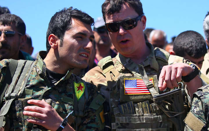 a US officer, from the US-led coalition, speaking with a fighter from the Kurdish People's Protection Units (YPG) at the site of Turkish airstrikes near northeastern Syrian Kurdish town of Derik.