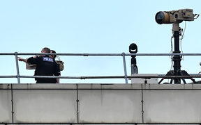 Police officers stand near equipment on the rooftop of a building at London Gatwick Airport, south of London.