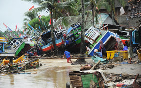 Fishermen tend to their traditional fishing boats which were damaged after being hit by a tsunami in the Teluk village, Labuan subdistrict in Banten province on 25 December, 2018.