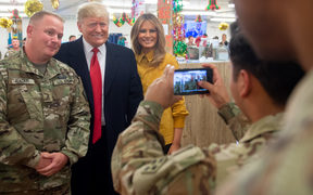 US President Donald Trump and First Lady Melania Trump take photos with members of the US military during an unannounced trip to Al Asad Air Base.