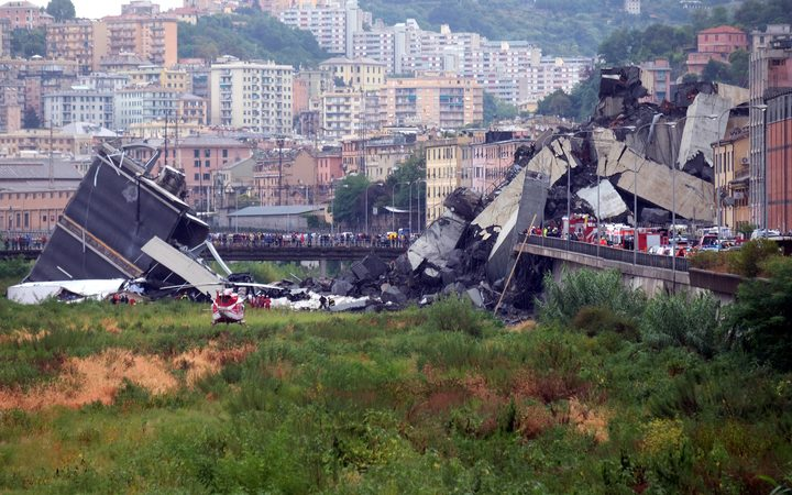 Another angle of the collapsed bridge shows rescuers scouring through the wreckage and people gathered around the scene.