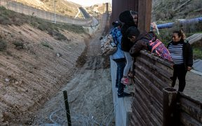 Central American migrants cross the US-Mexico border fence from Tijuana to San Diego County as seen from Tijuana, Baja California State, Mexico, on December 27, 2018.