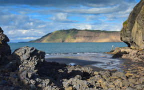 Cliffs and rock formations along black sand Whatipu Beach in Huia, West Auckland in New Zealand