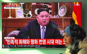 A woman walks past a television news screen showing a New Year speech by North Korean leader Kim Jong Un.