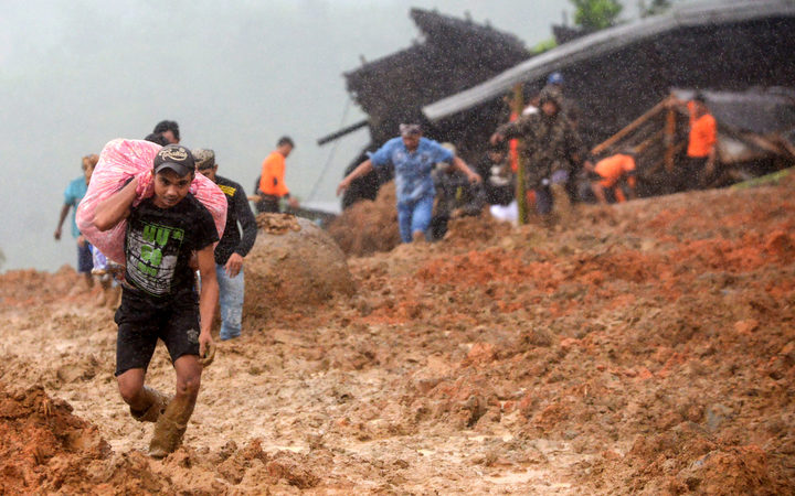 Residents evacuate their homes as rescue workers search for survivors at the site of a landslide triggered by heavy rain in Sukabumi, West Java province on January 1, 2019.