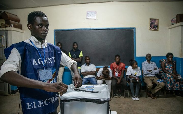 An Independent National Electoral Commission (CENI) agent seals a ballot box in front of observers at the Kitendo voting centre in Lubumbashi's Mapala district on December 30, 2018, following the close of polls in the country's presidential, provincial and national elections.  AFP
