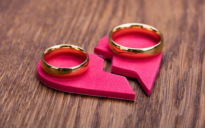69590501 - high angle view of golden ring on red broken heart at wooden desk