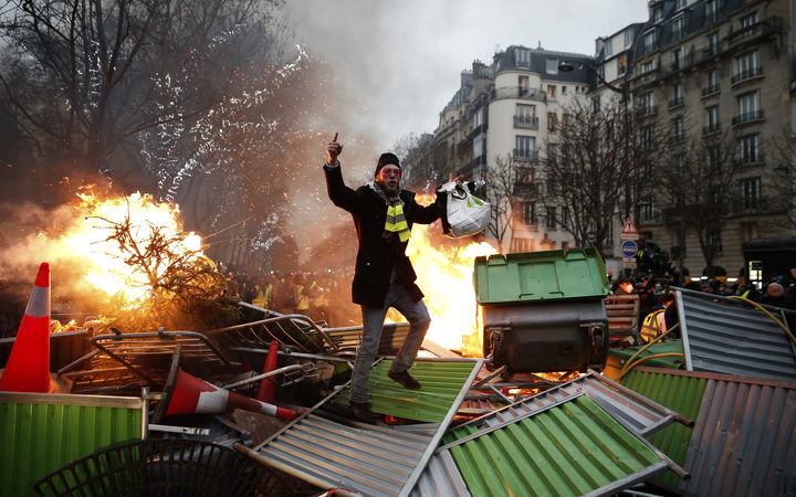 "A demonstrator gestures on a burning barricade on January 5, 2019 in Paris, during an anti-government demonstration called by the yellow vest ""Gilets Jaunes"" movement."