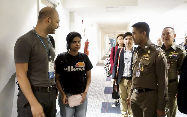 January 7, 2019 shows 18-year-old Saudi woman Rahaf Mohammed al-Qanun (2nd-L) is being escorted by the Thai immigration officer and United Nations High Commissioner for Refugees (UNHCR) officials at the Suvarnabhumi international airport in Bangkok.