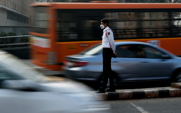 An Indian traffic policeman with his face covered by a protective mask handles traffic at an intersection in New Delhi