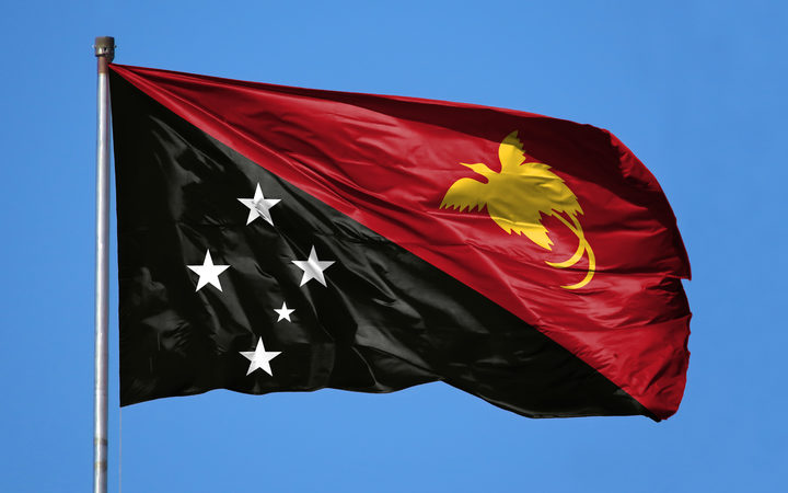 National flag of Papua New Guinea on a flagpole in front of blue sky.