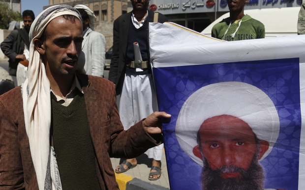 A man holds a portrait of Shia cleric Sheikh Nimr Baqir al-Nimr sentenced to death in Saudi Arabia
