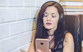 Biometric verification. Modern young woman with the phone. The concept of a new technology of face recognition on polygonal grid is constructed by the points of IT security and protection