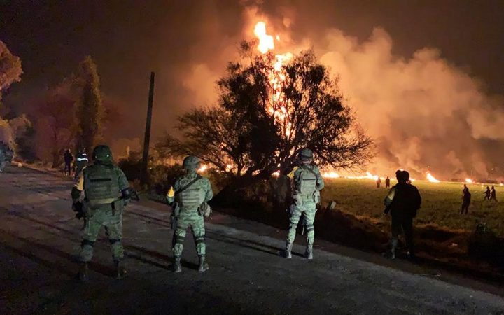 Mexican soldiers standing guard near a fire after a leaking gas pipeline triggered a blaze in Tlahuelilpan, Hidalgo state, on January 18, 2019.