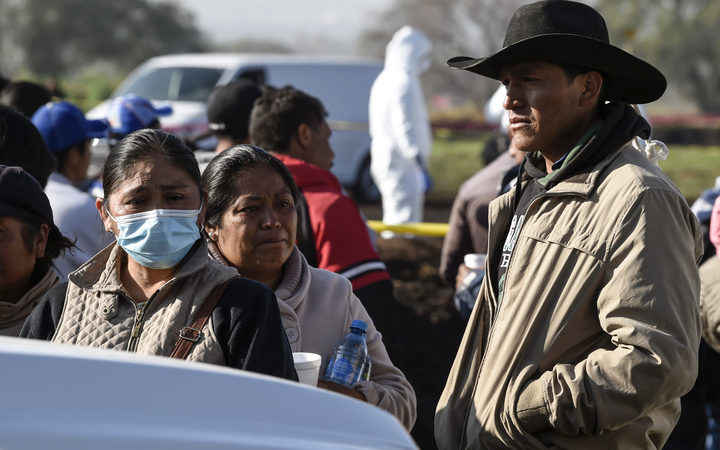 Relatives of victims wait at the scene of a massive blaze trigerred by a leaky pipeline in Tlahuelilpan.