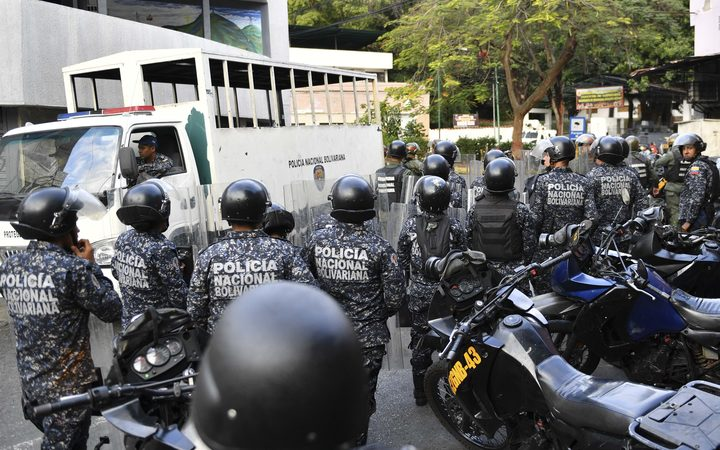 National Police officers remain outside the National Guard command post in Cotiza, in northern Caracas after a brief military uprising and amid opposition calls for mass protests.