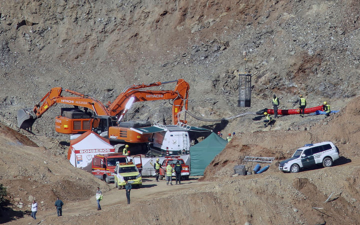 In this photo taken on Thursday, Jan. 24, 2019, drill and excavating machinery work on mountain next to a deep borehole to reach a 2-year-old boy trapped s near the town of Totalan in Malaga, Spain.