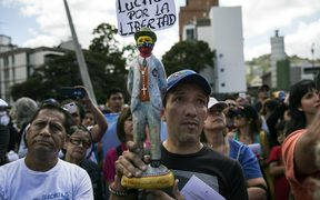 "A man holds a statuette of Venezuelan popular saint and  a sign that reads ""I fight for liberty,"" as members of the opposition gather to propose amnesty laws for the police and the military, in Caracas, Venezuela"