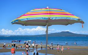 Colourful beach umbrella on a summer sunny day above unrecognizable people on a beach at the north shore of Auckland, New Zealand