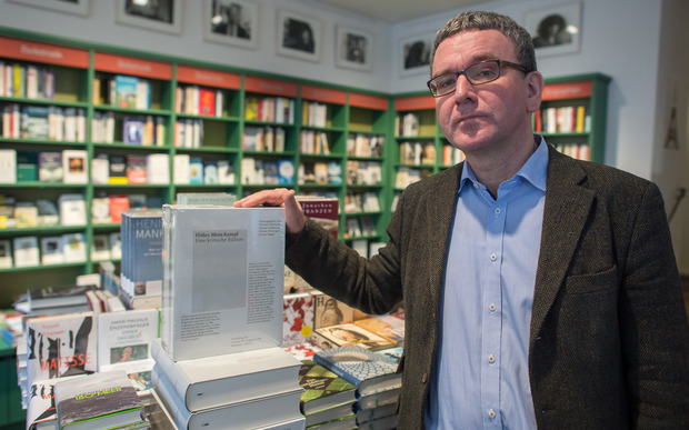 Michael Lemling, manager of the bookstore Lehmkuhl, poses next to a stack of editions of 'Hitler, Mein Kampf - eine kritische Edition' (lit. Hitler, My Struggle - a critical edition) at his bookstore in Munich, Germany.