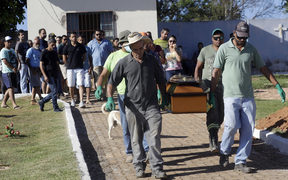 Cemetery workers carry the coffin with the body of Vale SA employee Edgar Carvalho Santos, victim of the collapsed dam, in Brumadinho, Brazil on Tuesday, 29 January.