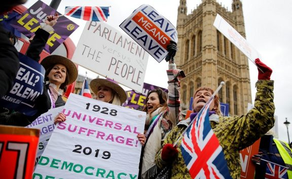 Pro-Brexit activists hold placards and wave Union flags as they demonstrate outside of the Houses of Parliament.