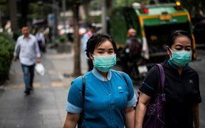 Pedestrians wearing face masks make their way along a street in Bangkok today.