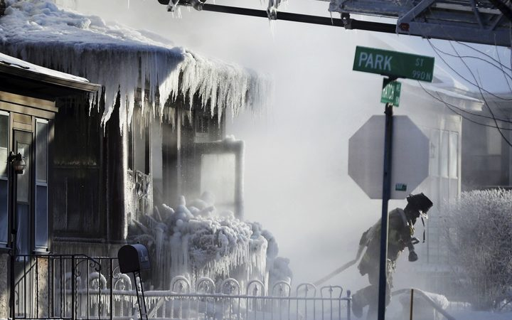 Firefighters at the scene of a house fire in Saint Paul, Minnesota during a arctic deep freeze on 30 January.