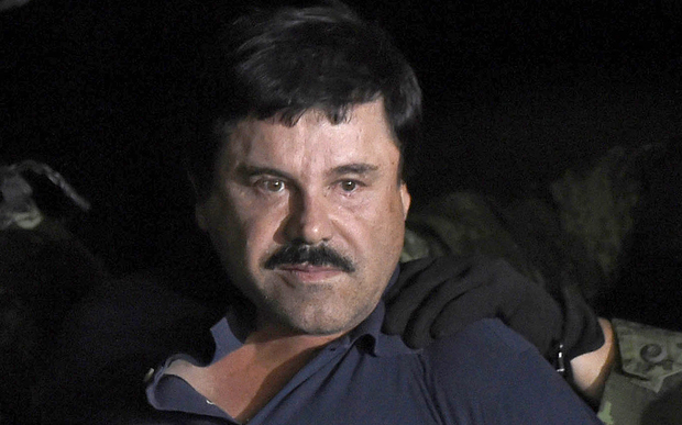 "Drug kingpin Joaquin ""El Chapo"" Guzman is escorted into a helicopter at Mexico City's airport."