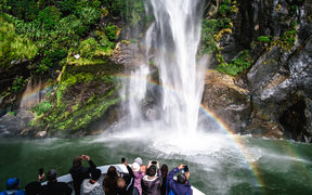 A group of tourists enjoying a stunning scene of nature while cruising into waterfall in Milford Sound, New Zealand.