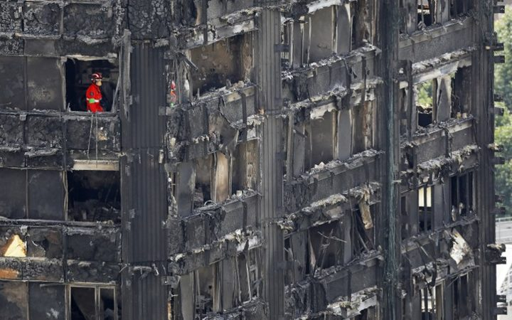Members of the emergency services work on the middle floors of the charred remnains of the Grenfell Tower block in Kensington, west London, on June 17, 2017, follwing the June 14 fire at the residential building.