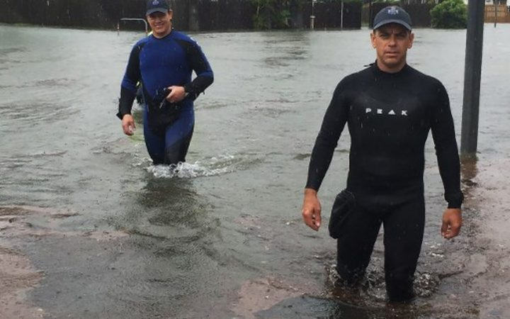 A handout picture provided by Queensland Police Service, taken on February 2, 2019 and release on February 3 shows two police officers wading in flood waters in Townsville. -