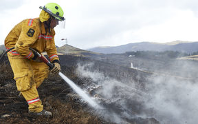 Fire fighter Lieutenant Oli Barnfather of the New Zealand Army fights an underground hotspot on the Port Hills of Christchurch.
