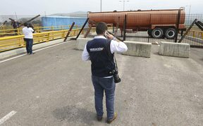 An immigration official observes a fuel tanker, cargo trailers and makeshift fencing, used as barricades by Venezuelan authorities trying to stop aid