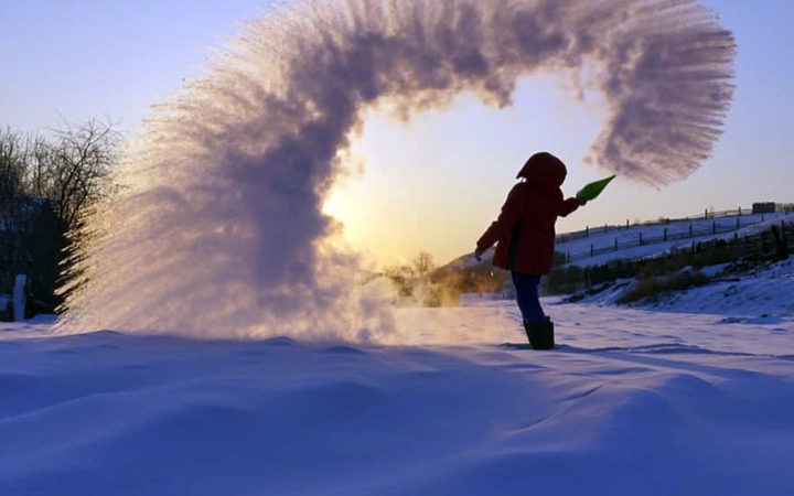In this handout photo taken on Tuesday, Feb. 5, 2019, a woman throws boiling water into the freezing air as its instantly condenses into an elaborate pattern of ice crystals in Irkutsk, Russia .