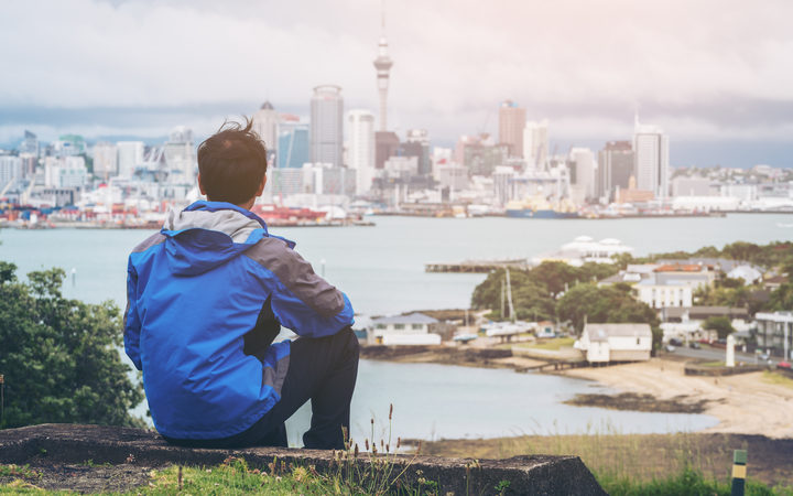 Young man at looking Auckland city skyline of city center and Auckland Sky Tower in New Zealand.