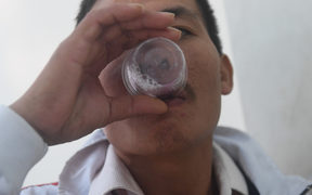 A recovering drug addict taking his daily dose of methadone at a treatment clinic.