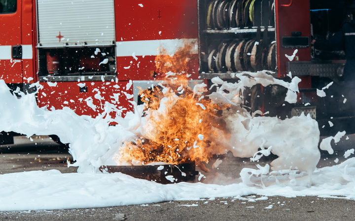 close up view of extinguishing foam, flame and fire truck on street